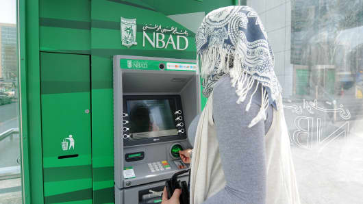 A customer uses an ATM machine near the National Bank of Abu Dhabi headquarters.