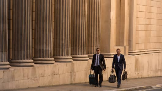 Businessmen carry bags past a bank, financial