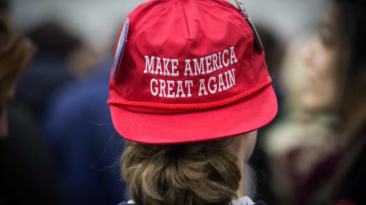 "A supporter wearing a hat with the Trump campaign slogan, ""Make America Great Again."""