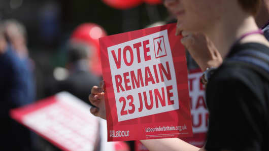 Students hold Vote Remain posters as former Labour leader Ed Miliband campaigns for remain votes while touring with the Labour in Battle bus at Flag Market on May 24, 2016, in Preston, England.