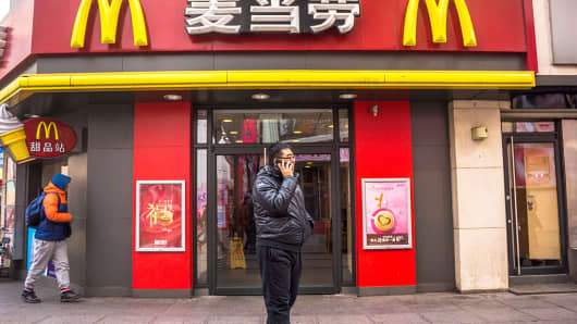 A man stands infront of a McDonald's restuarant in Tianjin, China on February 2, 2015. McDonald's has received more than half a dozen bids for its planned sale of China and Hong Kong stores, including offers from Beijing Tourism Group, Sanpower and ChemChina in a deal worth about $3 billion.