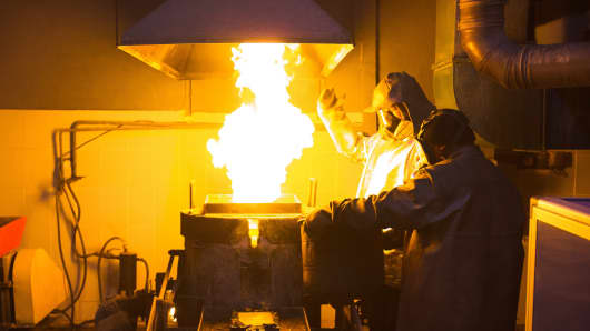 Workers use a furnace to melt gold during the casting of gold ingots at the Suzdal gold mine, operated by Nordgold NV, in Semey, Kazakhstan.
