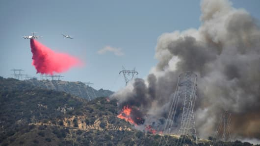 A fire fighting aircraft (L) drops fire retardant as its spotting plane (R) follows above power lines over one of two wildfires in the Angeles National Forest above Azusa, California.
