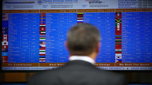 A pedestrian looks at prices displayed on digital screens at a foreign currency exchange bureau in London, U.K., on Wednesday, June 22, 2016.