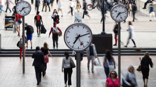 Pedestrians walk past clocks in the Canary Wharf financial, shopping and business district in London, U.K., on Tuesday, June 21, 2016.