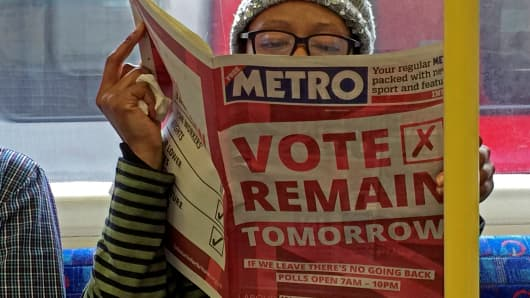 DATE IMPORTED:June 22, 2016A woman reads a newspaper on the underground in London with a 'vote remain' advert for the BREXIT referendum, Britain June 22, 2016.