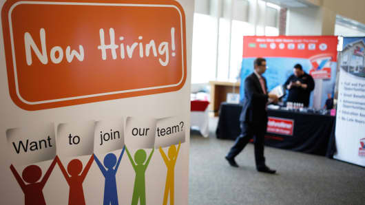 A 'Now Hiring' sign is displayed during a Job News USA career fair in Louisville, Kentucky.