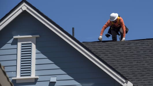 A worker attaches roofing to a house under construction at the KB Home Magnolia at Patterson Ranch community in Fremont, California.