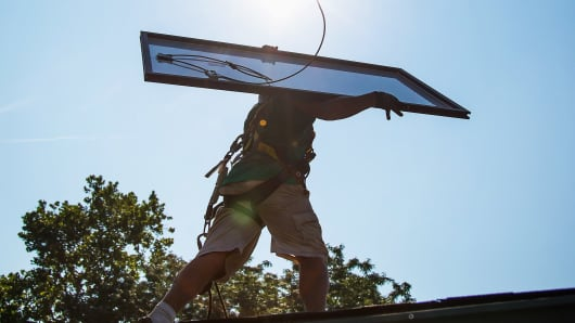 A SolarCity employee carries a solar panel on the roof during installation at a home in Kendall Park, N.J.