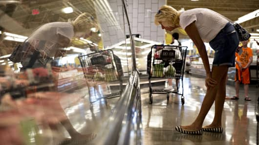 A shopper browses the fresh meat case at a Kroger-owned store in Orland Park, Illinois.