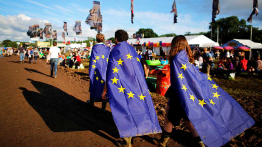 People wrapped in European Union flags walk at Worthy Farm in Somerset during the Glastonbury Festival, Britain, June 22, 2016.
