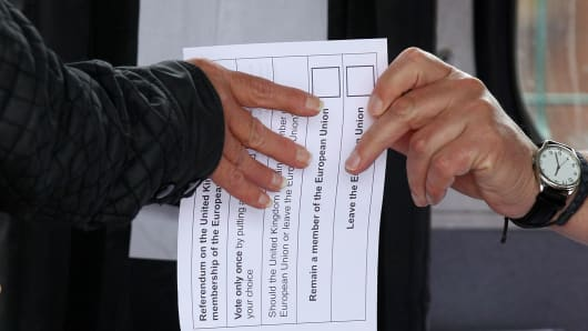 A volunteer hands an unmarked ballot paper to a voter inside a bus being used as a temporary polling station in Kingston-Upon-Hull, northern England, on June 23, 2016, as Britain holds a referendum to vote on whe