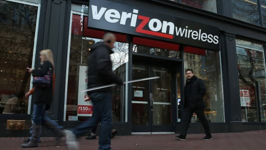 Pedestrians walk by a Verizon Wireless store on January 22, 2015 in San Francisco, California.