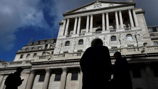 City workers walk past the Bank of England in the City of London, Britain