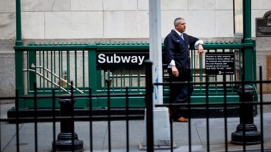 A trader stands in front of a subway station near the New York Stock Exchange in New York.