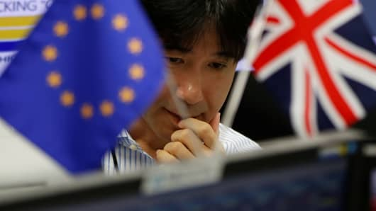 An employees of a foreign exchange trading company works as he is seen between British Union flag and an EU flag in Tokyo, Japan, June 24, 2016.