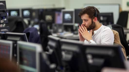A trader monitors financial data on computers screens at ETX Capital, a broker of contracts-for-difference, in London, U.K.