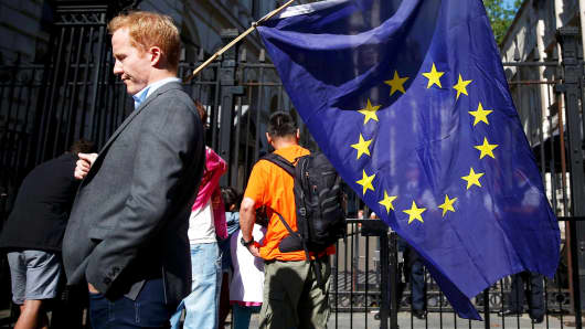 A man carries an EU flag, after Britain voted to leave the European Union, outside Downing Street in London, June 24, 2016.