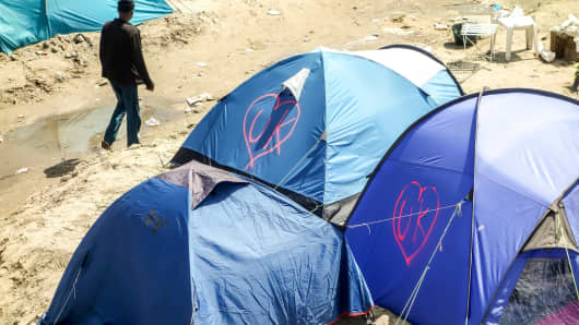 The initials of the United Kingdom, UK, are seen tagged into a heart-shape logo onto some tents of migrants inside the 'Jungle' camp for migrants and refugees in Calais on June 24, 2016.