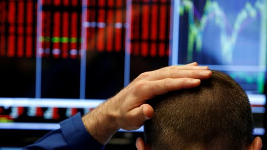 A trader touches his head as he works on the floor of the New York Stock Exchange (NYSE) in New York, U.S., June 24, 2016.