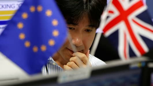 An employee of a foreign exchange trading company works between a British flag and an EU flag
