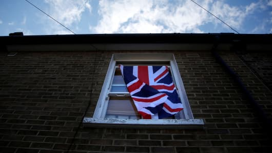A British flag flutters in front of a window in London on June 24, 2016 after Britain voted to leave the European Union.
