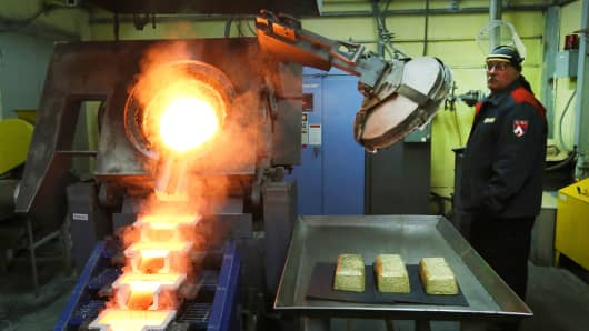 A worker pours molten gold into 25 kilogramm molds at the Verninsky GOK gold mine and processing plant, operated by Polyus Gold International Ltd., near Bodaybo, Russia.