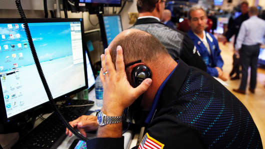 A trader talks on the phone as he works on the floor of the New York Stock Exchange.
