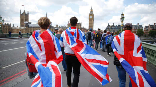 People walk over Westminster Bridge wrapped in Union flags, towards the Queen Elizabeth Tower (Big Ben) and The Houses of Parliament in central London on June 26, 2016.