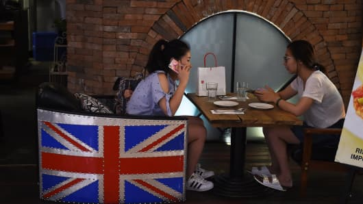 A woman sits in a restaurant chair decorated with the British flag in Beijing on June 27. The Brexit vote added new uncertainties at a time when downward pressures on China's economy were mounting, Chinese Premier Li Keqiang said a day later.