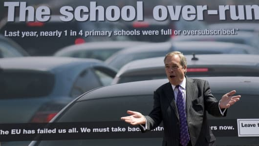 UK Independence Party (UKIP) leader Nigel Farage poses in front of a new campaign poster in Clacton-on-Sea, eastern England on June 21, 2016.