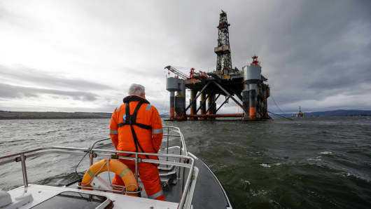 An employee stands on the deck of a pilot boat in view of the Ocean Princess oil platform, operated by Diamond Offshore Drilling Inc., in the Port of Cromarty Firth in Cromarty, U.K.