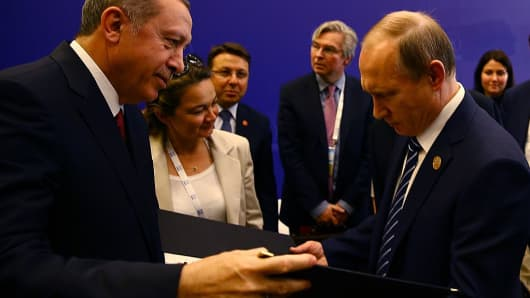 Turkish President Recep Tayyip Erdogan (L) presents personalized stamps to Russian President Vladimit Putin (R) on November 16, 2015.