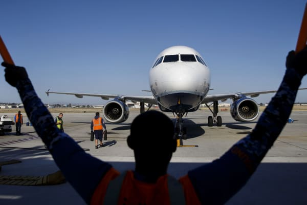 An aircraft marshaller guides a JetBlue Airways aircraft at the Long Beach, California, airport.