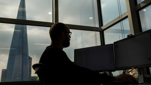 An employee looks at financial data on computer screens, in front of a view of The Shard building, on the trading floor at Bats Europe, the European arm of Bats Global Markets Inc., in London, U.K.