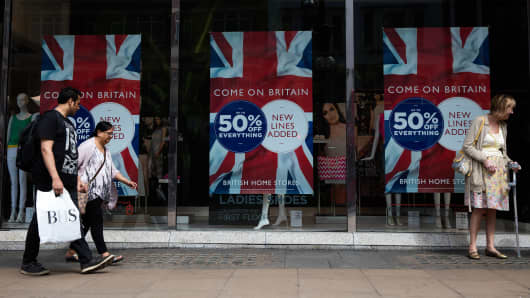 Pedestrians walk past British Union flag designs on advertisements for sales discounts