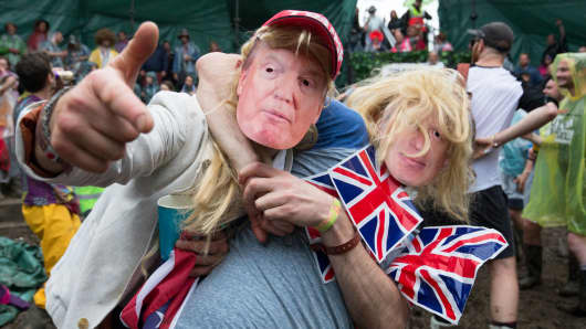 Men dressed as Donald Trump and Boris Johnson prepare to take part in a tomato fight at the Glastonbury Festival 2016 in England.
