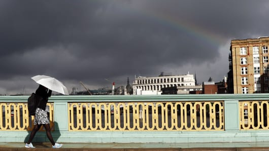A commuter shelters herself from the rain beneath her umbrella as she walks under a rainbow into the city of London across Southwark Bridge in Central London on June 27, 2016.