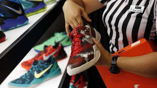 An employee arranges Nike basketball shoes on display