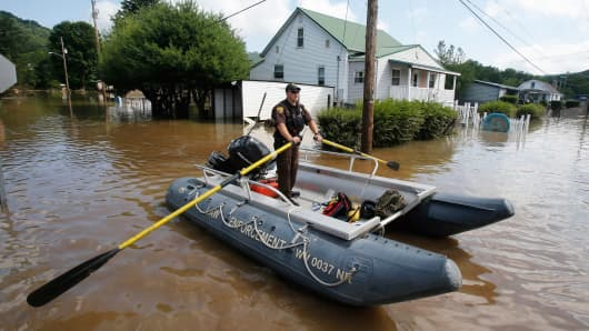 Lt. Dennis Feazell, of the West Virginia Department of Natural Resources, rows his boat as he and a co-worker search flooded homes in Rainelle, W. Va., June 25, 2016.