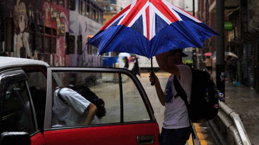 A man closes his umbrella designed like the British flag as he enters a taxi with his companion during a downpour in Hong Kong on June 28, 2016.