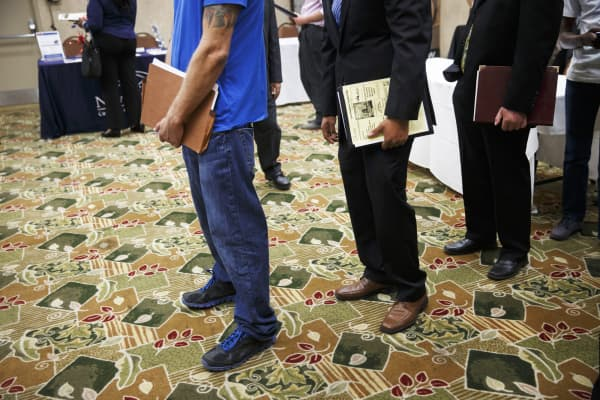Job seekers wait in line to speak with representatives during a Choice Career Fair in Los Angeles.