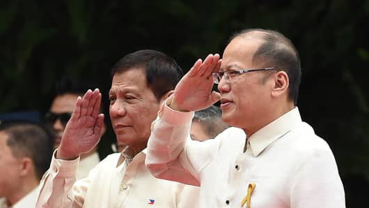 Outgoing Philippines President Benigno Aquino (R) and his successor Rodrigo Duterte (center-L) salute during the departure ceremony for Aquino ahead of the swearing-in at Malacanang Palace in Manila on June 30, 2016.