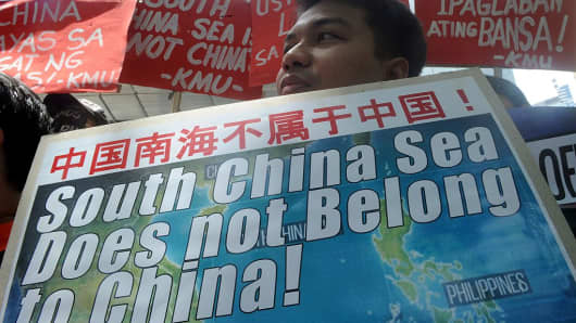 A protestor holds a placard at a rally in front of the Chinese Consulate in Manila's financial district on July 7, 2015, denouncing China's claim to most of the South China Sea including areas claimed by the Philippines.