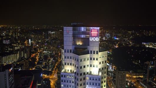 The United Overseas Bank Ltd. (UOB) logo is illuminated at night atop UOB Plaza One in Singapore, on Wednesday, March 20, 2013.