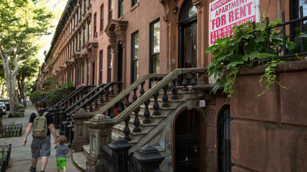 People walk past brownstone townhouses in the Fort Greene neighborhood