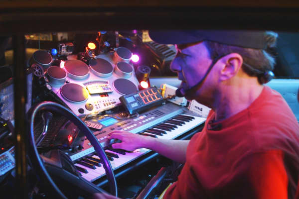 Jon Barnes prepares the keyboard, drums, and light panels he operates while driving his Ultimate Taxi around Aspen, Colorado.