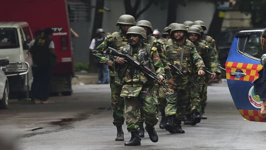 Bangladeshi army soldiers patrol a street during a rescue operation as gunmen take position in a restaurant in the Dhakas high-security diplomatic district on July 2, 2016.