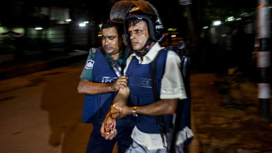 An injured Bangladeshi policeman being assisted after a granade attack at a restaurant nearby in the early hours of July 2, 2016 in Dhaka, Bangladesh.