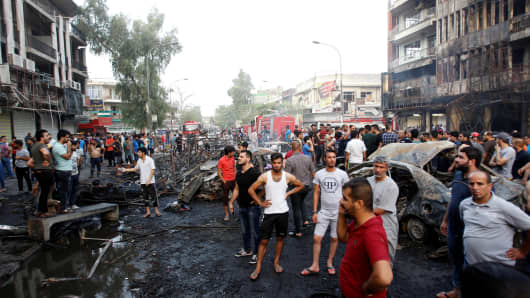 People gather at the site of a suicide car bomb in Baghdad, Iraq July 3, 2016.